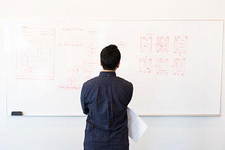 een man die naar een whiteboard kijkt.