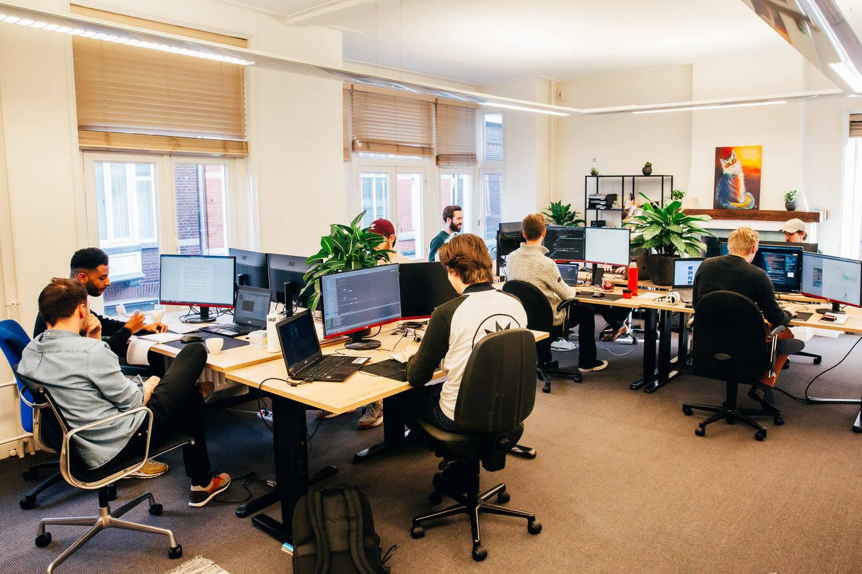 Het team van Scrumble werkend achter computers in hun kantoor.
