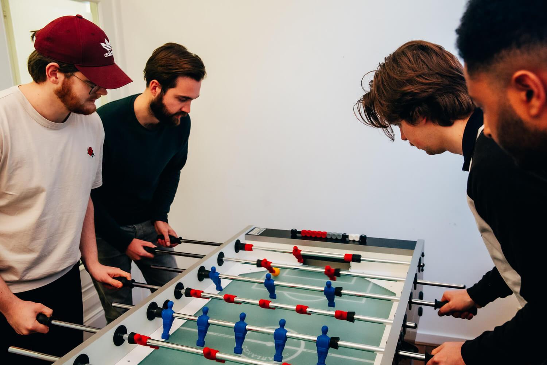foto van het team van scrumble tijdens een potje tafelvoetbal