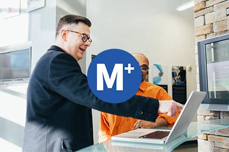 logo van M+ op een foto van twee mannen die naar een laptop kijken, waarvan er 1 aan het wijzen en uitleggen is