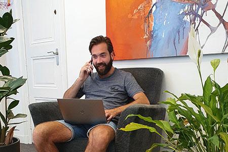 Scrumble medewerker die lachend aan het telefoneren is met een laptop op zijn schoot op een fauteuil