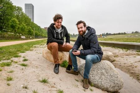 Luuk en Vincent zittend op stenen in het Spoorpark