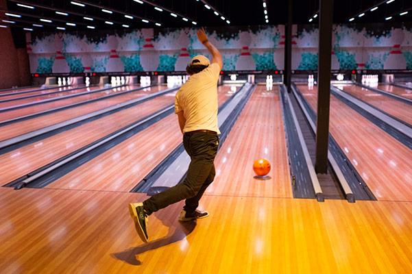 medewerker van Scrumble die een bal gooit op de bowlingbaan